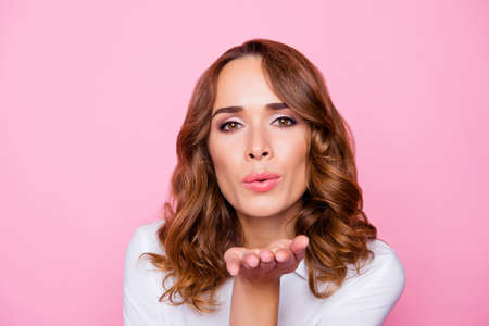 Close up portrait of attractive charming lovely woman with perfect hairdo and excellent make up, she is sending an air kiss, isolated on bright pink background