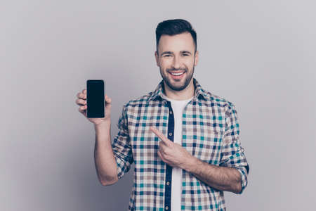 Portrait with copy space of young, smiling man recommend to do online shopping using smart phone, presenting, indicating on brand, new mobile phone over grey background