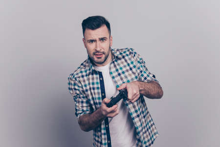 Portrait of young bearded brunet guy holding joy stick, playing video game over grey background Stock Photo