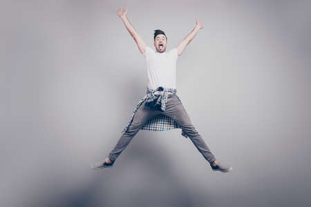 Happiness, freedom, motion and people concept - happy  attractive handsome young man with bristle jumping in air like star with raised hands and opened legs, showing tongue over grey background Stock Photo