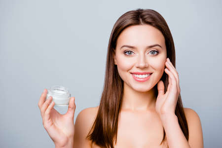 Concept of using moisturizing cream before going to bed. Beautiful cute pretty charming woman is holding a cream jar and applying it on her skin, isolated on grey background