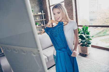 Ich möchte dieses elegante schöne blaue Kleid tragen! Hübsche lächelnde glückliche aufgeregte frohe herrliche Blondine versucht auf neuem Kleid vor einem Spiegel Standard-Bild