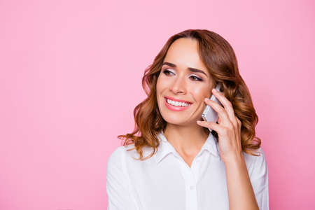 Close up portrait of smiling happy joyful peaceful carefree attractive woman calling to her best friend, isolated on vivid bright pink background Banque d'images