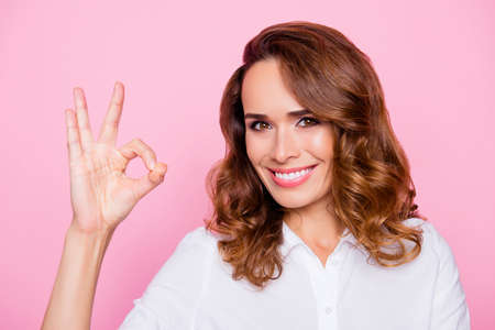 Everything is done in a proper way! Close up portrait of beautiful charming woman with toothy beaming shiny smile, she is demonstrating ok sign, isolated on bright pink background