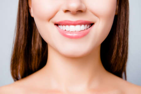 Concept of healthy wide beautiful smile. Cropped close up photo of healthy without caries shiny toothy woman's smile, isolated on grey background