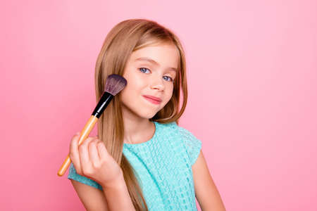 Close up portrait of little beautiful daughter using her mums make up brush for applying cosmetics on skin, isolated on bright pink background, copyspace