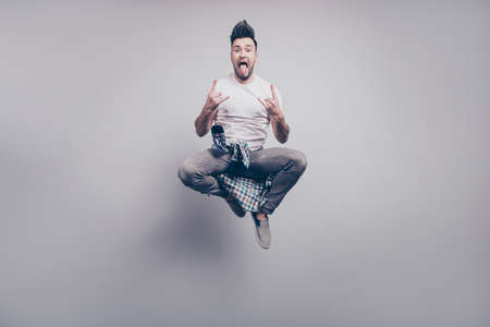 Happiness, freedom, motion and people concept. Crazy, bearded attractive handsome music lover jumping in air, gesturing rock and roll sign with hair up and tongue out over grey background