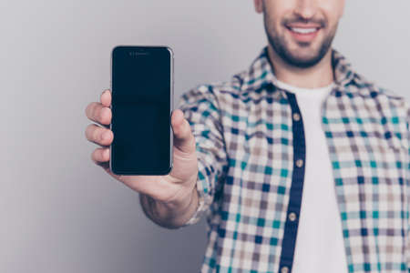 Close up portrait with copy space of black screen of smart phone demonstrating by cheerful, confident, professional, brunet guy with half face in checkered shirt over grey background