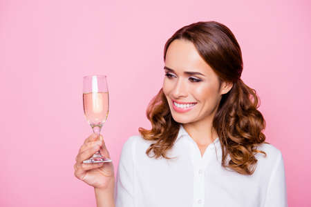 Close up portrait of beautiful joyful delightful woman with toothy smile holding a glass of champagne, isolated on bright pink background Stock Photo