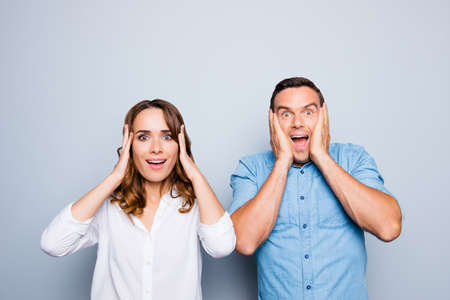 Portrait of sweet, attractive, lovely, cute, cheerful, mature, adult, shocked couple holding hands on head with wide opened eyes and mouth, unsuspected facial expression over grey background Stock Photo