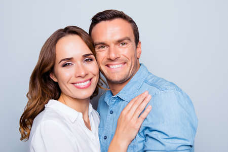 Close up portrait of mature, adult, attractive, cute, lovely couple with beaming smiles, check to check face, looking at camera,   over grey background