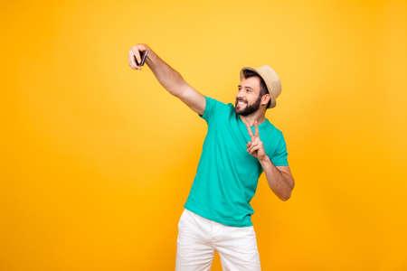 ねえどう。彼の新しいスマートフォンに自画像を撮り、2本の指を示すカジュアルな衣装に身を着た幸せなファンキー陽気な喜びの男、コピースペー
