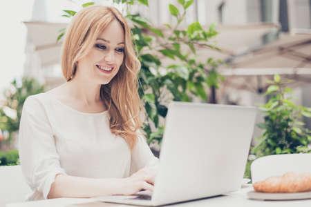 Vrij modieuze vrouw die aan computer buiten werkt
