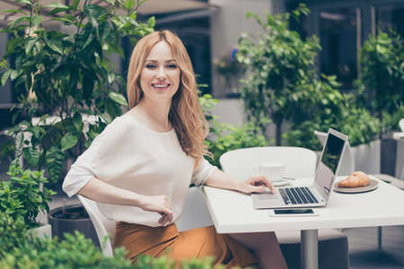 Attractive, pretty, elegant manager using modern devices working in the cafe, she is repeat client of this restaurant Stock Photo