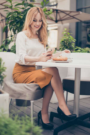 Young attractive woman sitting in a cafe in the morning before her work and planning tasks for the whole day