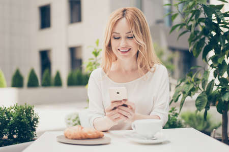 Young businesswoman having brunch at a cafe, using mobilephone, communicate with her lover through free wi fi