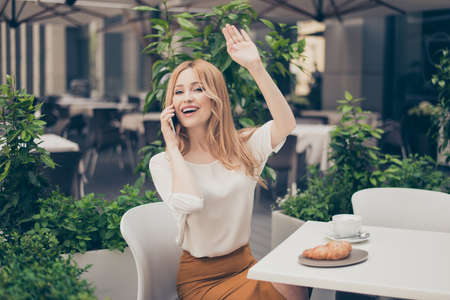 Young happy businesswoman, repat client,   having lunch in the cafe, talking on smart phone, raised her hand up, greeting her friend