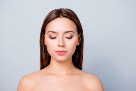 美しい女性の顔のクローズアップ写真、彼女の目が閉じている、彼女は完璧なメイクアップと髪型を持って、灰色の背景に隔離され、コピースペー 写真素材
