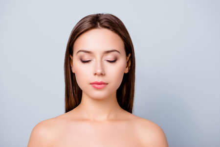 Close up photo of beautiful woman's face, her eyes are closed, she has perfect make up and hairdo, isolated on grey background, copyspace