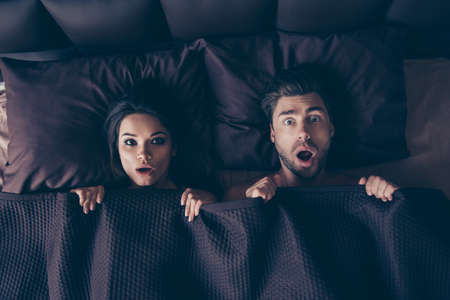 Top view photo of two shocked beautiful surprised people with open mouths, covering their bodies with blanket in bedroom