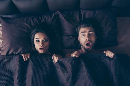Foto di vista superiore di due persone sorprese bella sorpresa con le bocche aperte, che coprono i loro corpi con coperta in camera da letto