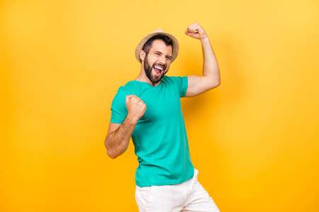 Gelukkige opgewekte vrolijke joyous kerel die zijn overwinning met opgeheven die handen vieren, op gele achtergrond wordt geïsoleerd