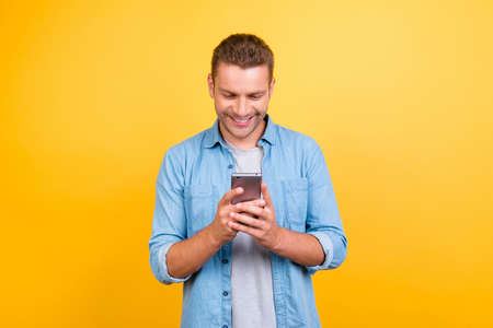 Bearded, cheerful, attractive guy in casual outfit, jeans shirt, holding smart phone in hands, using 3G internet, wi-fi, checking email, doing online shopping over yellow background