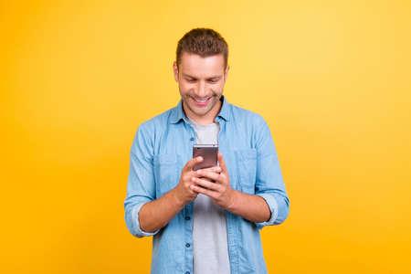 Chico barbudo, alegre y atractivo con atuendo informal, camisa de jeans, sosteniendo el teléfono inteligente en las manos, usando internet 3G, wi-fi, revisando el correo electrónico, haciendo compras en línea sobre fondo amarillo