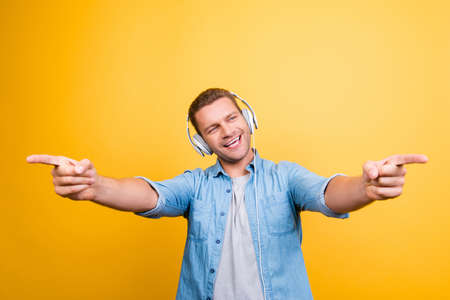 Portrait of caucasion, positive guy in jeans shirt with bristle listening his favorite music, singing the song, pointing index fingers front over yellow background Stock Photo