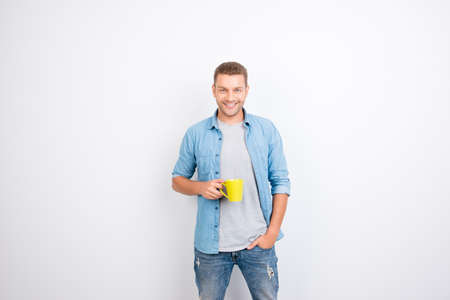 Portrait of cheerful, peppy guy holding yellow mug with coffee and one hand in pocket, getting a charge of vivacity, looking at camera, standing over white background Stock fotó