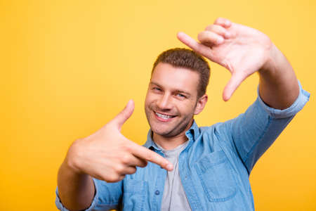 Closeup of young, happy man with stubble making diagonal frame in front of face with fingers, over yellow background Stock Photo