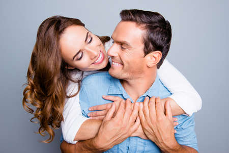 Close up portrait of mature, adult, attractive, lovely, cute, sweet spouses, charming woman hugging man from back and they looking to each other, holding hands over grey background