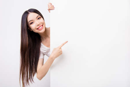 Funky asian young girl with long hair is looking out of a blank white clean banner or billboard, she is pointing on empty copy space, she is isolated on grey background Stock Photo