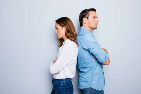 Portrait of unhappy frustrated couple standing back to back not speaking to each other after an argument while standing on grey background. Negative emotion face expression reaction 版權商用圖片