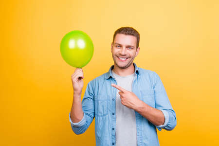 Smiling cheerful guy pointing with forefinger to green balloon standing over yellow background