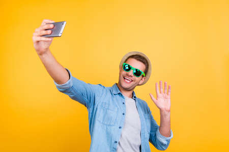Stylish, cheerful, bearded guy in casual outfit  taking a picture of himself, using smart phone, wi-fi internet, having video call with friends, sending greetings with palm over yellow background Reklamní fotografie