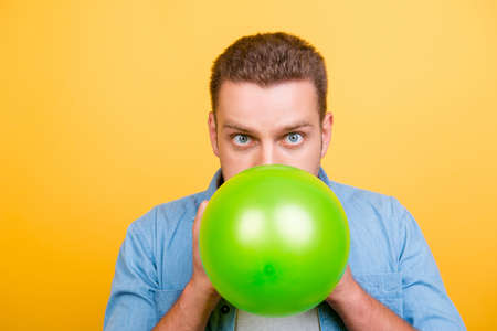 Young, amazed, stylish blond man is blowing green balloon for birthday party and looking at the camera with wide open eyes over yellow background