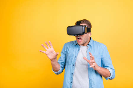 Close up of impressed, scared guy in jeans shirt wearing virtual reality goggles, getting experience using VR-headset, gesticulating, gesturing with  hands  while over yellow background Imagens