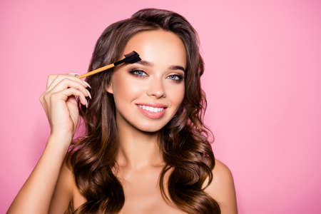Tätowierung, Microblading, Brauen modellieren, Perfektionskonzept. Attraktive wunderschöne charmante Dame mit idealem Gesicht, gesunde glänzende klare Haut, erstaunliche Frisur, hält Pinsel in der Hand, malen ihre Augenbrauen