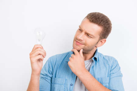 Close up portrait of thinking blond student with bristle with idea, touching chin with hand, holding, looking at  light bulb while standing over white background
