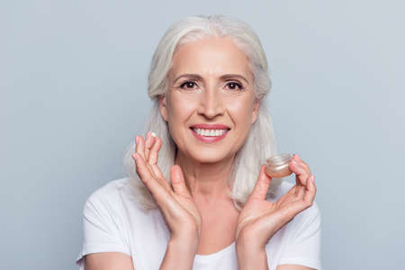 Close up portrait  of senior, attractive, pretty, nice,  woman with beaming smile holding, having, applying anti-aging, for dry skin cream, lotion over grey background