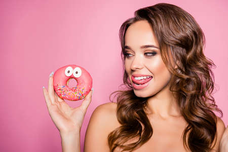 Wow! Healthcare, willpower, summer, bodycare, concept. Close up portrait of cheerful coquette lady holding yummy cakes, with sticking tongue, looks with desire at unhealthy treat