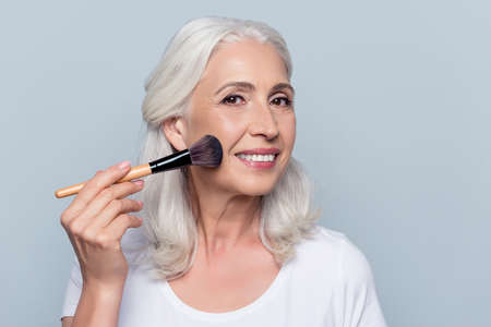Middle aged, attractive, caucasian, nice woman applying makeup on her face, using powder, rouge, holding tassel in hand, making cheekbones over grey background