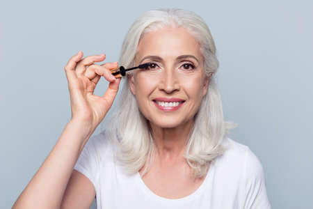 Leuke, opgetogen, blanke, charmante, mooie, oude vrouw die zwarte mascara, verfwimpers met kwastje aanbrengen, maken, professionele make-up doen over grijze achtergrond