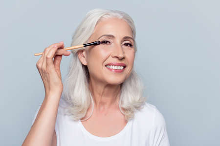 Nice, delighted, caucasian, attractive, aged woman applying eyeshadow, using tassel, making, doing professional make up over grey background