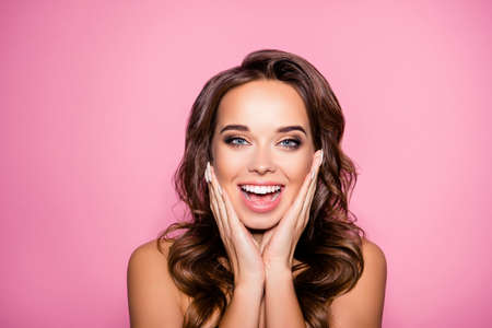 Aging, acne, pimples, wrinkles, oily, dry skin concept. Close up cropped photo of pretty excited lady with wavy hairdo, arm palms near face, happiness and freshness, purity