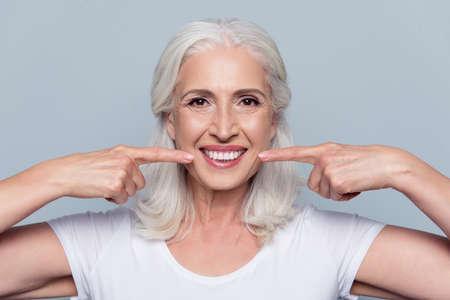 Conceito de ter dentes brancos retos saudáveis fortes na idade avançada. Feche acima do retrato de feliz com radiante sorriso feminino pensionista apontando em seus dentes brancos claros perfeitos, isolado no fundo cinza