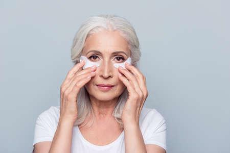 Retrato da avó bonita, agradável segurando patches, tendo sacos sob os olhos pela manhã por causa de menos sono, mostrando um efeito de pele perfeita sobre fundo cinza