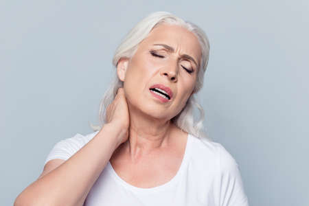 Aged, pretty, attractive, nice woman feeling exhausted, holding hand on neck, chilled, stretched out, suffering from pain with close eyes over grey background, health care concept