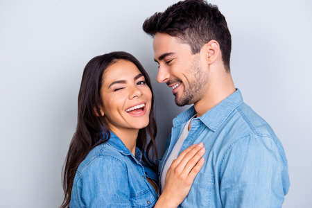 Close up portrait of caucasion lovely couple - smiling man with bristle looking at his funny, cute woman who laugh, blink and looking at camera  standing over grey background Archivio Fotografico